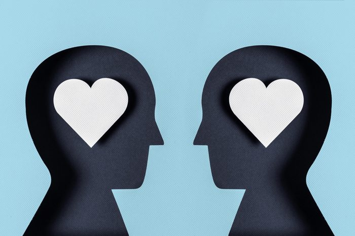 two paper silhouette heads with hearts in their brains