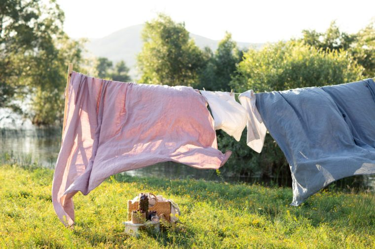 Clean bed sheet hanging on clothesline.
