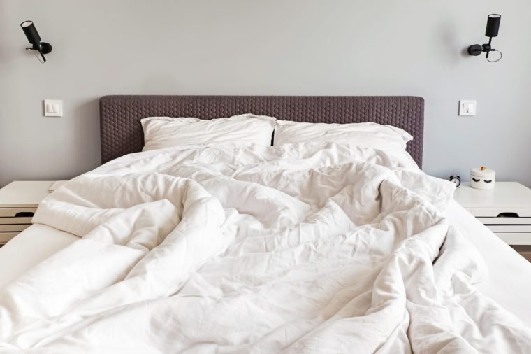 Unmade messy bed with white bedsheet in the morning.