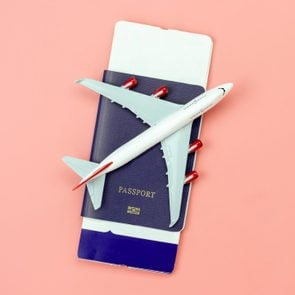 model airplane on a passport with tickets inside. peach background.