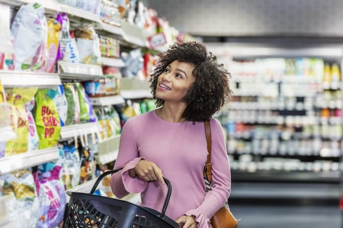 Young African-American woman shopping in supermarket