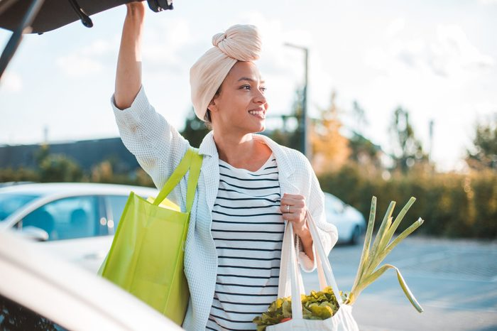 Girl holding groceries and closing trunk