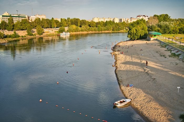 People sunbathing on the shore of Dniester River in Tiraspol, Transnistria