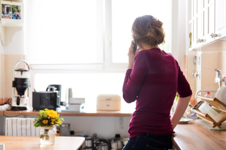 A young woman at home in the kitchen is using a telephone, while looking out of the window