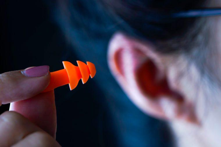 Female hand putting orange earplugs