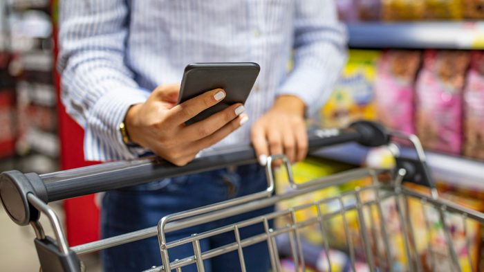 Woman using mobile phone to compare price