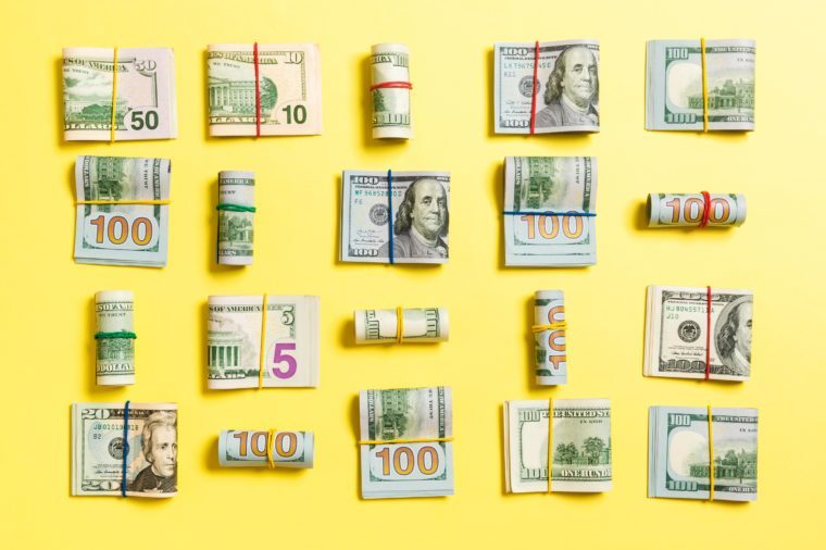 wads of bills on yellow background
