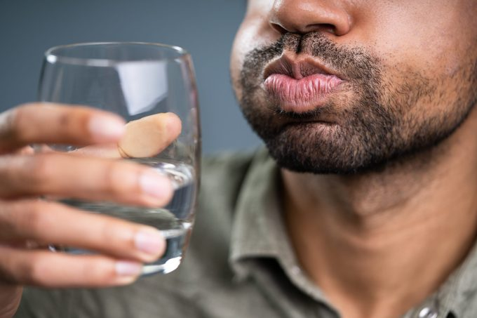 Man Rinsing And Gargling With Water In Glass