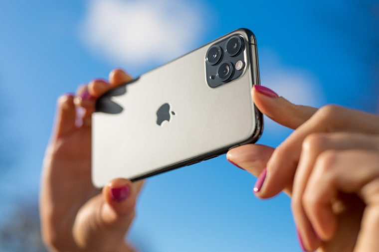 apple iphone 11. womans hands holding phone horizontally.