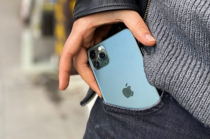 man's hands pulling iphone 11 out of pocket. close up.