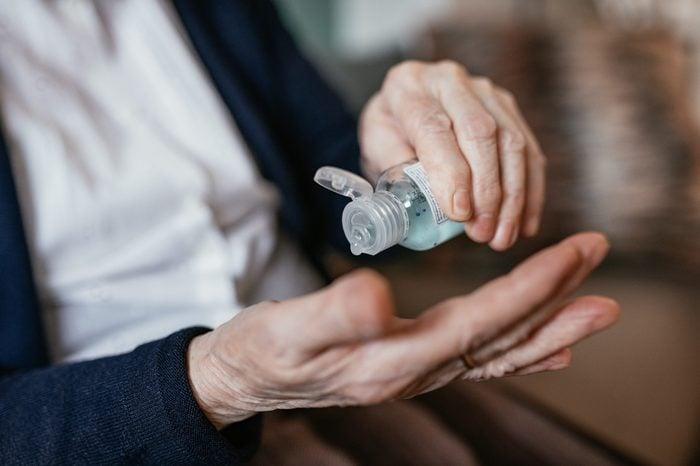 Senior woman applying hand sanitizer at home