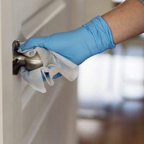 Hand with glove wiping doorknob.