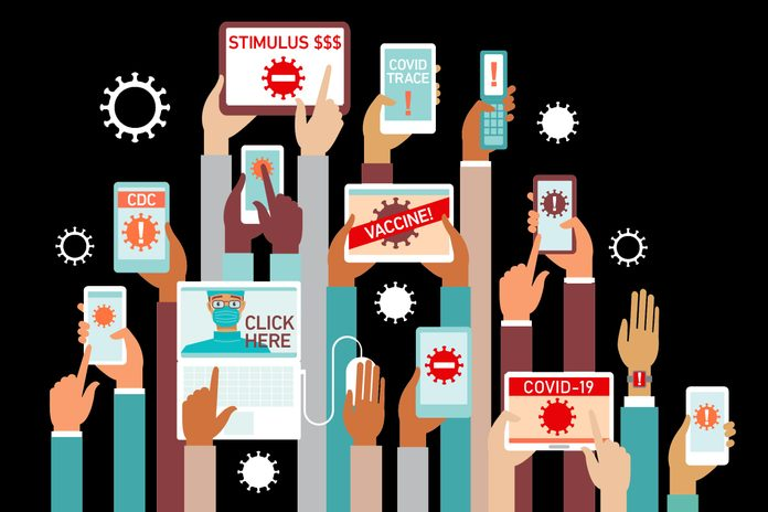 many hands reaching up holding various smartphones and devices showing covid-19 scams