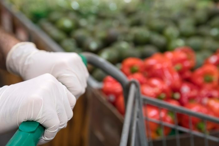 Man wearing protective gloves shopping in the supermarket.