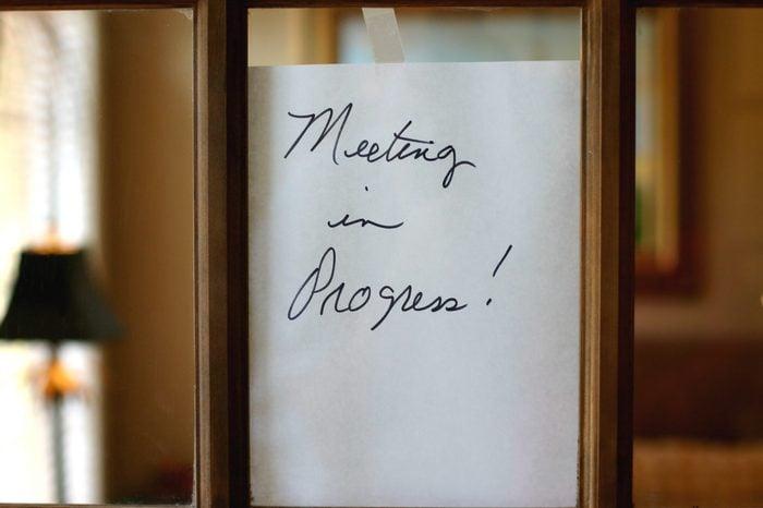 Meeting in Progress Sign on Glass Door