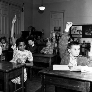 In a school classroom, all the students but one raise their hands to answer a question, New York, New York, 1948.