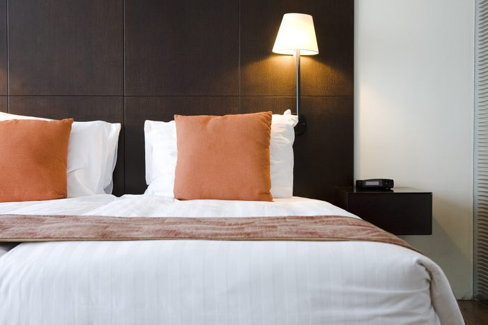 Bed in hotel room with orange pillows
