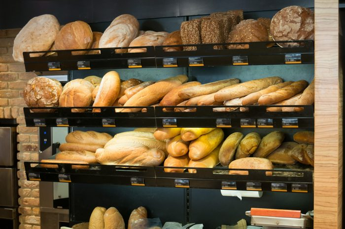 Different types of fresh bread and rolls on sale at a bakery