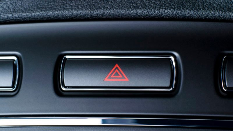 Vehicle, car hazard warning flashers button with visible red triangle.