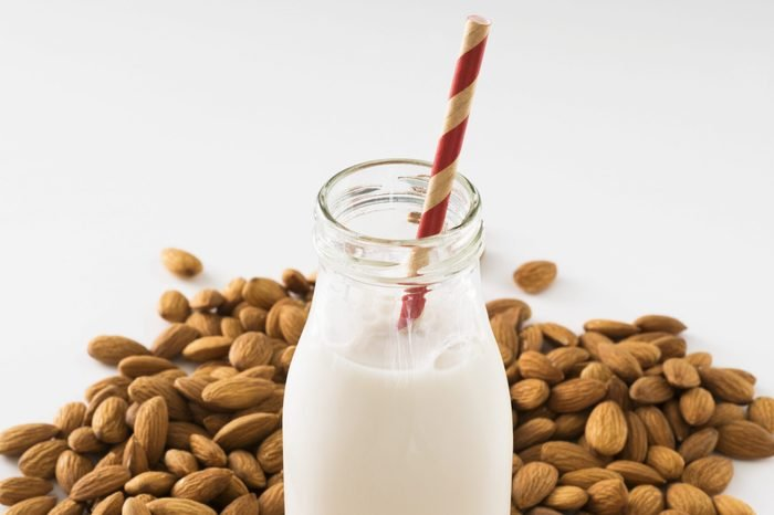 A glass milk jug filled with organic almond milk. The drink is sitting in the middle of a raw almond pile.