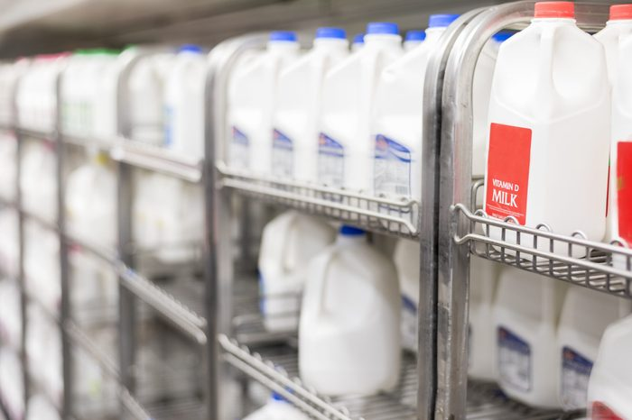 shelves of refrigerated milk in store