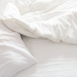 Top view of an unmade bed with crumpled bed sheet.