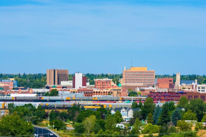 Cheyenne, Wyoming, downtown skyline with train cars, houses, and trees in view.