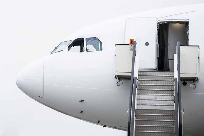 Airplane nose with open cabin doors and movable stairs