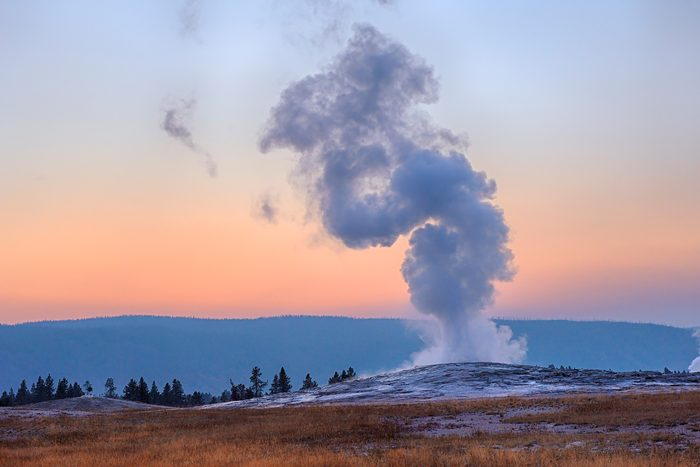 USA, Wyoming, Yellowstone National Park, Old Faithful Geyser erupting at sunset