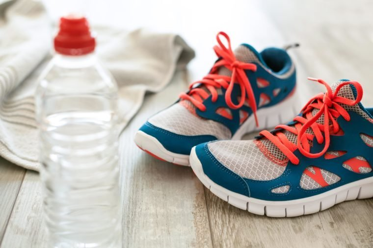 sneakers and water bottle on wood floor