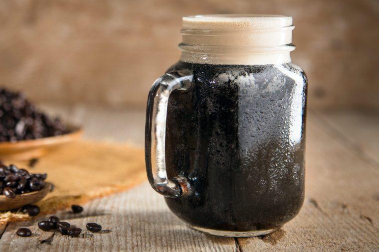 Dark rich beautiful froth foam nitro black coffee jar java