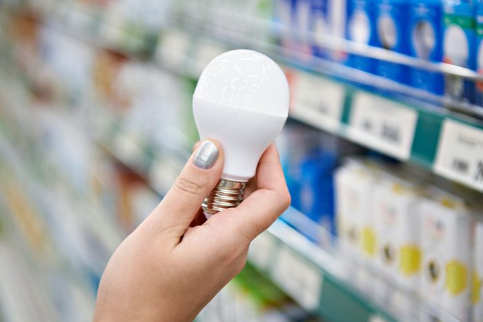 Energy saving LED lamp in hands of buyer at store
