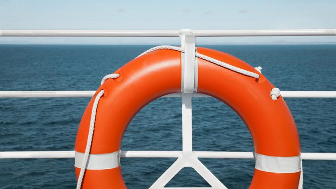 life preserver hanging on the railing on a deck of a cruise ship. seascape background.