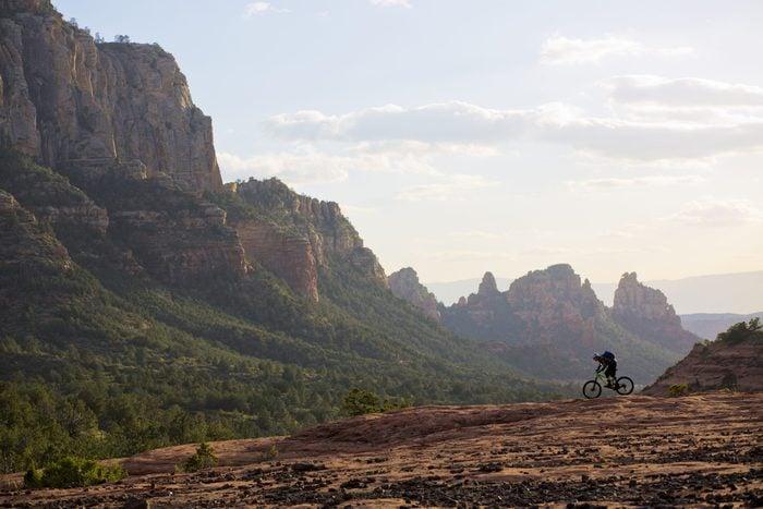 A man rides his enduro-style mountain bike at the end of the day in Sedona, Arizona, USA.