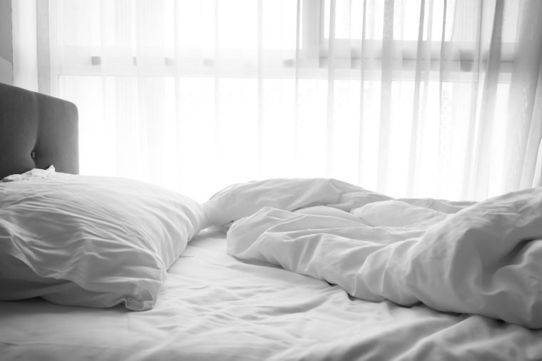 Messy bed. White pillow with blanket on bed unmade. Concept of relaxing after morning. Dark vignette.