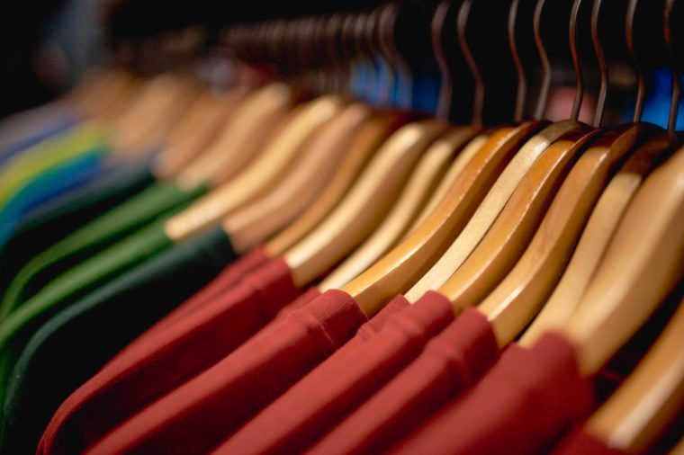 rack of clothes, close up, in a retail store. colored t-shirts on hangers.