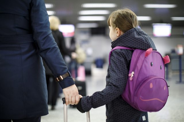 Mother and daughter pulling together a suitcase