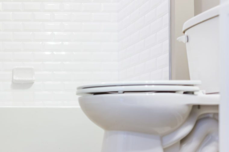 Modern white plain clean toilet bathroom with shower tiles and hardwood floors from ground level