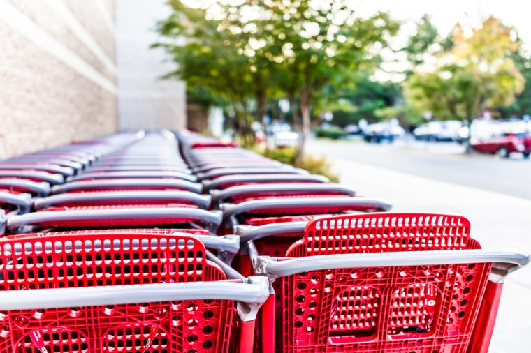 Many rows of red shopping carts outside by store with closeup by parking lot