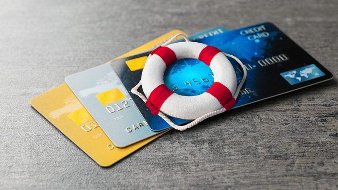 three credit cards on and a miniature life preserver on a wooden desk