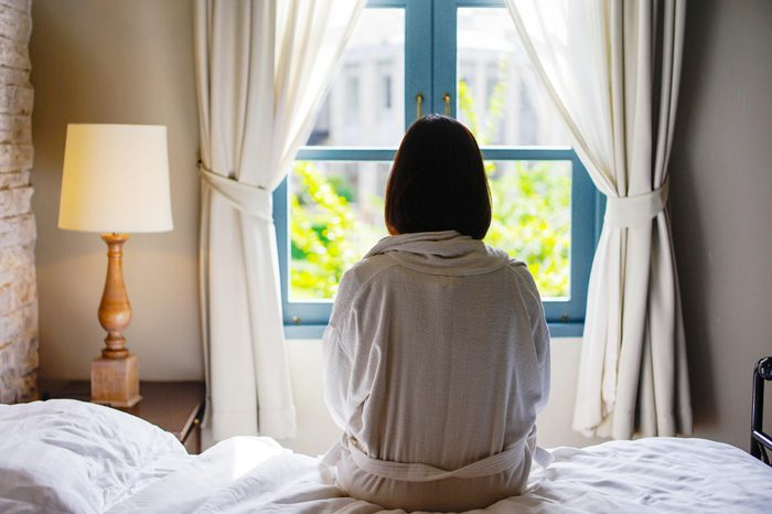 woman sits on the edge of the bed looking out window