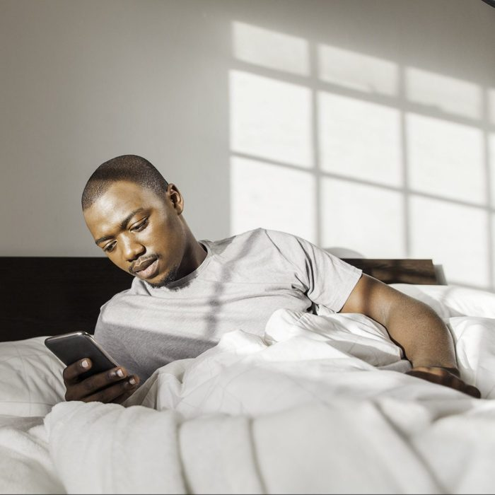 Businessman Waking Up In Bed Texting On His Phone In The Morning.