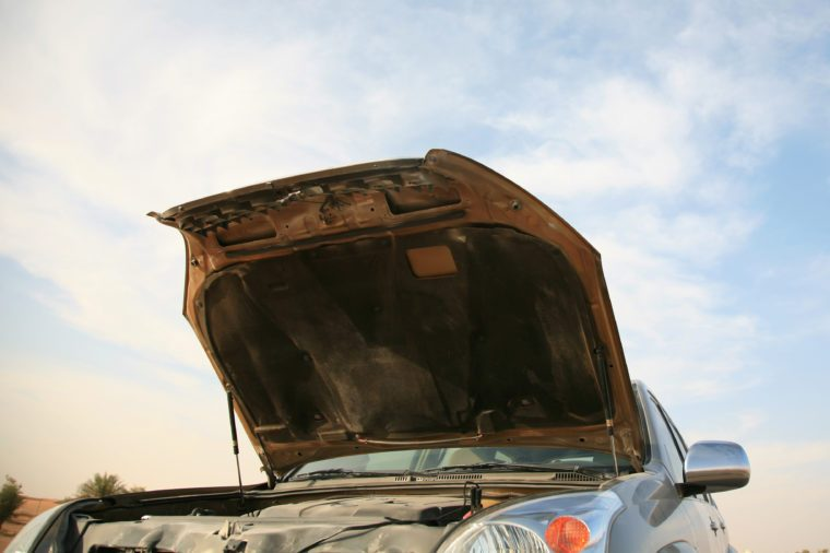 Lifted hood of a car showing damage inside