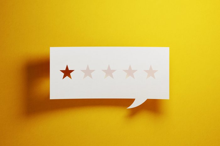 Feedback Concept - White Chat Bubble With Cut Out Star Shapes Over Yellow Background