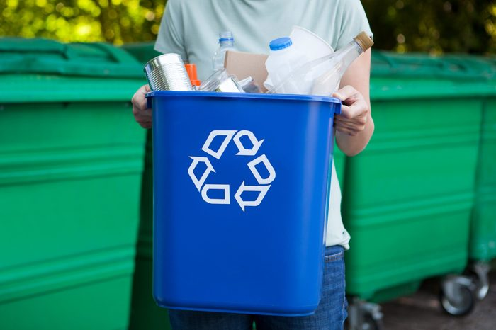 Close Up Of person Carrying Recycling Bin