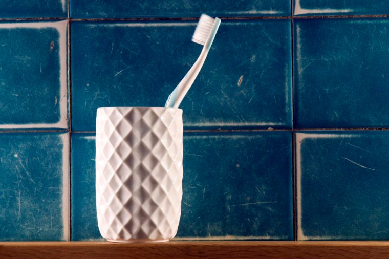 Single toothbrush in white beveled cup against blue tile