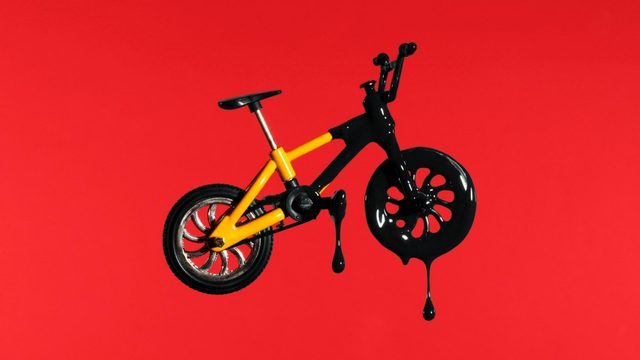 yellow bicycle dripping with black paint on red background
