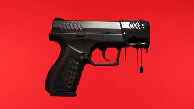 gun dripping with black paint on red background