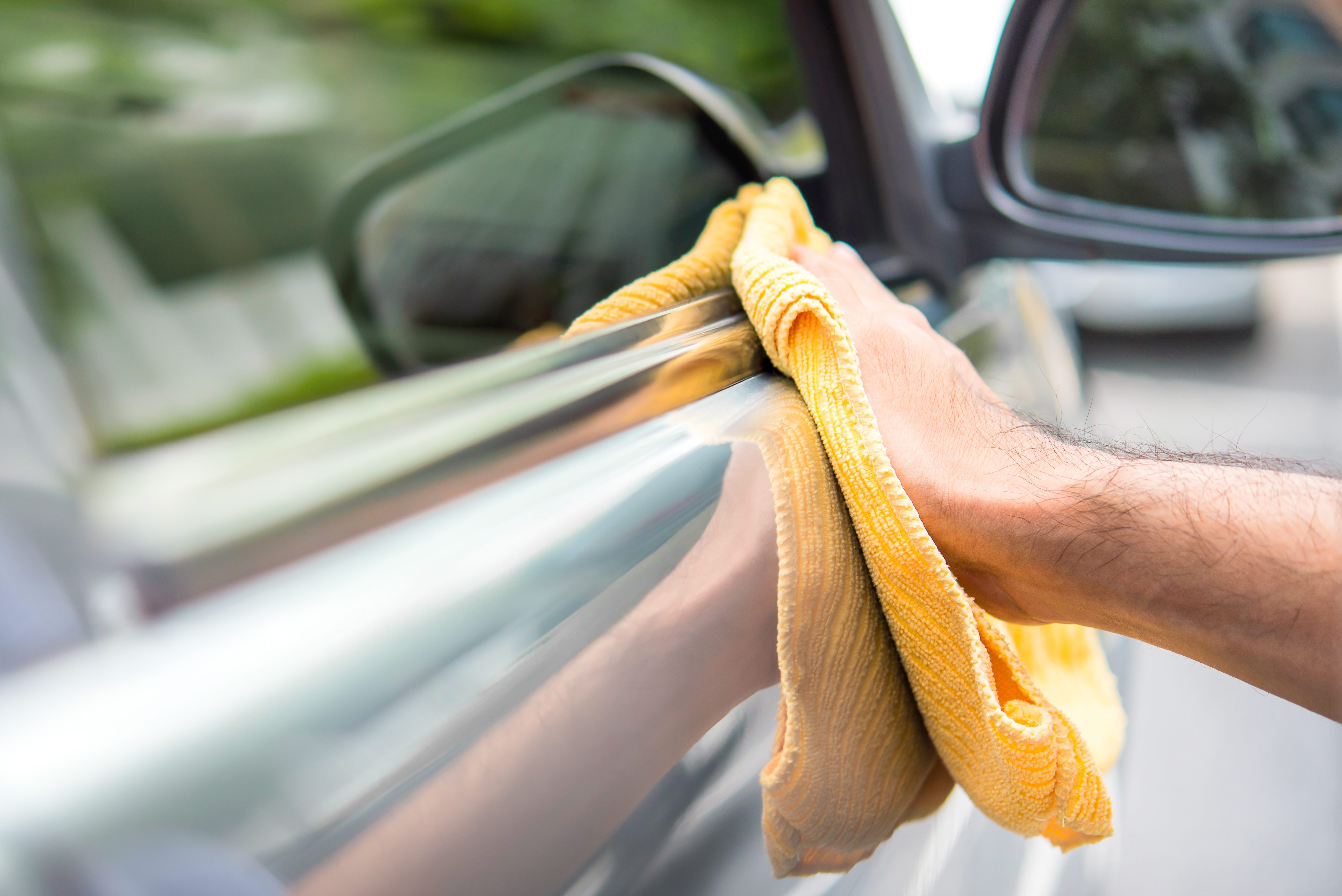 A man cleaning a car with yellow microfiber cloth - car detailing, vale and auto service concept