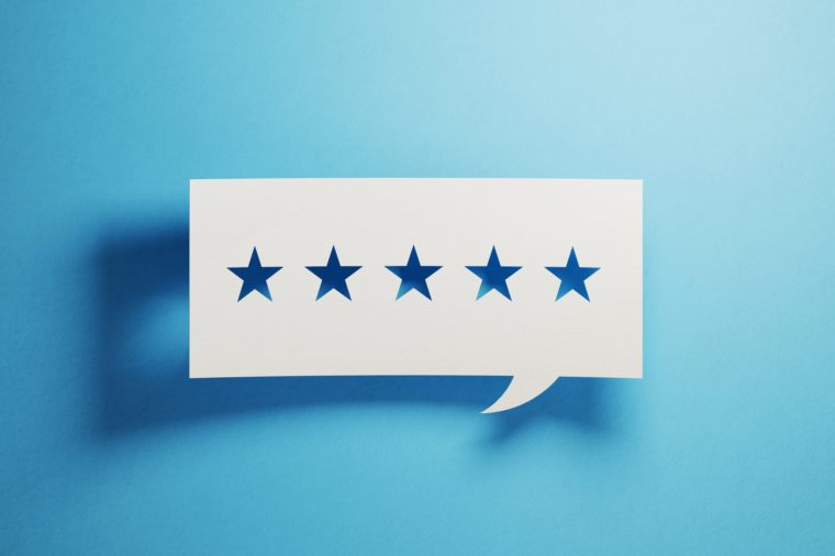 Feedback Concept - White Chat Bubble With Cut Out Star Shapes Over Blue Background